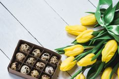 Easter spring decorative composition. Bouquet of yellow tulips tied by green ribbon and little box with quail eggs. Close up portr. Ait on white wooden Stock Image
