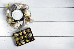 Easter spring decorative composition, crafted wreath with candle inside and box with quail eggs. Close up portrait on white wooden. Background with place for Royalty Free Stock Photo