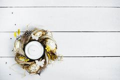 Easter spring decorative composition, crafted wreath with candle inside. Close up portrait on white wooden background with place f. Or text Royalty Free Stock Photo