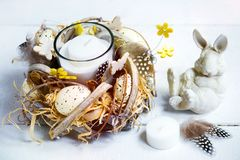 Easter spring decorative composition, crafted wreath with candle inside, white bunny and box with quail eggs. Close up portrait on. White wooden background Royalty Free Stock Photos