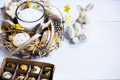 Easter spring decorative composition, crafted wreath with candle inside, white bunny and box with quail eggs. Close up portrait on. White wooden background with Stock Photography