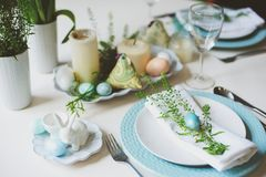 Easter and spring festive table decorated in blue and white tones in natural rustic style, with eggs, bunny, fresh flowers. And candles Royalty Free Stock Photography