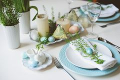 Easter and spring festive table decorated in blue and white tones in natural rustic style, with eggs, bunny, fresh flowers. And candles royalty free stock photo