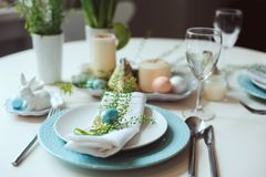 Easter and spring festive table decorated in blue and white tones in natural rustic style, with eggs, bunny, fresh flowers. And candles Stock Image