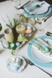 Easter and spring festive table decorated in blue and white tones in natural rustic style, with eggs, bunny, fresh flowers. And candles Royalty Free Stock Images