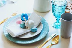 Easter and spring festive table decorated in pink and blue colours with modern golden metallic cutlery. Eggs and bunny Stock Photo
