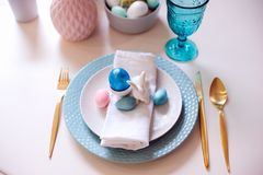 Easter and spring festive table decorated in pink and blue colours with modern golden metallic cutlery. Eggs and bunny Stock Image