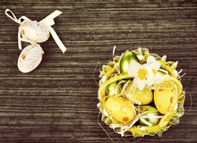 Easter.Spring flowers and eggs in yellow basket Stock Image
