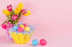 Easter spring home decor of yellow tulips, painted eggs, two eggs on pastel soft pink background. royalty free stock photo
