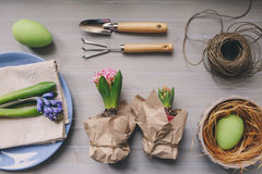 Easter and spring preparations. Hyacinth, eggs and garden tools on table, top view Royalty Free Stock Photos