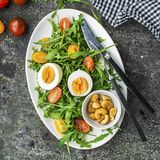 Easter spring salad with fresh vegetables: tomatoes, arugula, egg, nuts and croutons on a gray grunge background. Top. View royalty free stock photos