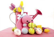 Easter Spring theme pink watering can with easter eggs and handmade crochet knit wool bunny Royalty Free Stock Photos