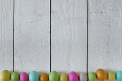 Easter or Spring Themed Background of Old Wood and Colored Eggs Royalty Free Stock Images