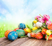 Easter still life. Hand-painted easter eggs with blooming tulips Stock Photos