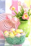Easter still life. With eggs in basket, bonnet and tulips in vase Stock Images