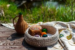 Easter still life as jug and knitted pottle with colored eggs inside stays on the aged wooden table with tablecloth under blooming stock photo