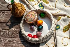 Easter still life as jug and knitted pottle with colored eggs inside stays on the aged wooden table with tablecloth under blooming royalty free stock images