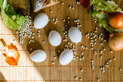 Easter still life on bamboo mat. Still life with cereals, bread, onion, eggs and greens on a bamboo Mat Royalty Free Stock Photo