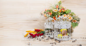 Easter still life. Bird cage with quail eggs and spring flowers Royalty Free Stock Images