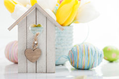 Easter still life with bird house. Easter decoration with eggs, bird house and tulip flowers Stock Photos
