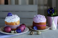 Easter still life, Easter cake, chicken and quail eggs, on a violet and gray textile background. royalty free stock image