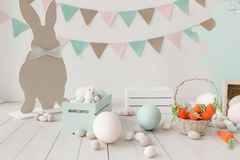 Easter still-life with eggs, carrots bunny paper silhouette and garland on wall. Copy space background