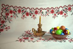 Easter still life. Orthodox Easter. On a table covered with a tablecloth with ornaments worth plate with colored eggs. Nearby stands a candle in a candlestick Royalty Free Stock Photos