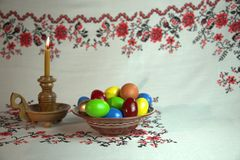 Easter still life. Orthodox Easter. On a table covered with a tablecloth with ornaments worth plate with colored eggs. Nearby stands a candle in a candlestick Royalty Free Stock Images