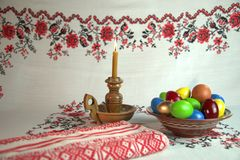 Easter still life. Orthodox Easter. On a table covered with a tablecloth with ornaments worth plate with colored eggs. Nearby stands a candle in a candlestick Stock Image