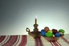 Easter. Easter still life. Orthodox Easter. On a table covered with a towel with ornaments worth plate with colored eggs. Nearby stands a candle in a Stock Images