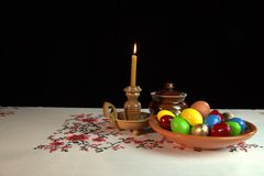 Easter still life. Orthodox Easter. On the table is a plate with colored eggs. Nearby stands a candle in a candlestick. Black background. Under the alpha Stock Images
