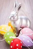 Easter still life with a silver bunny and eggs Stock Images