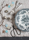 Easter still life. Vintage plate, fork, scissors, quail eggs, paper garland, branches on a grey table, top view. Royalty Free Stock Photography
