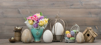 Easter stillife. Tulip flowers and colored eggs Stock Photo