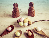 Easter sugar coated candy eggs on wooden and silver spoons with Stock Image