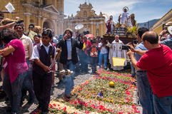 Easter Sunday procession, Antigua, Guatemala. ANTIGUA, GUATEMALA - APRIL 8, 2012: Easter Sunday procession walking over carpet made of flowers in front of Stock Images