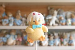 Easter Sweet, a baby chick wears Easter egg hat. Easter jelly candy with soft window light and abstract blur of a shelf decorated royalty free stock image