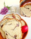 Easter sweet bread, cozonac. Traditional Romanian Easter sweet bread named cozonac. With red egg on a plate and a candle. Vertical white background stock images