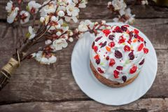 Beautiful Easter cake stands on a wooden texture surface, near lies flowering apricot. place under text. Easter sweet bread Orthodox kulich, paska, willow twigs Royalty Free Stock Photo