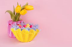Easter sweet vanilla pink background with painted eggs, tulips bouquet, and copy space. Stock Photos