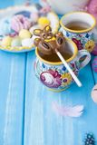 Easter sweets for the holiday. Spring. Bright colors on coffee mugs. Chocolate bunny. View from above. Vertical photo. royalty free stock images