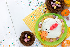 Easter sweets and treats: Easter eggs, Easter chick fondant cake. And candy mini eggs on white background top view stock photos