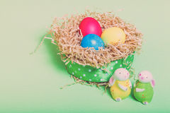 Easter symbols - colored eggs and bunny on light background. Ton Royalty Free Stock Photos