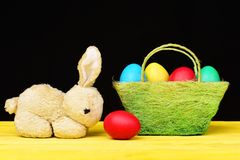 Easter symbols composition. Toy bunny and painted Easter eggs in different colours standing on yellow wooden table stock photo