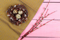 Easter symbols. A nest with eggs and willow on a pink. Top view stock image