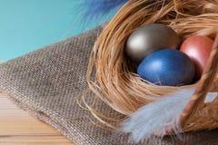 Easter tło z Wielkanocnymi jajkami w koszu na drewnianym tle fotografia royalty free