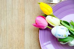 Easter table. Easter background with a lilac plate, a nicely decorate egg and fresh tulips on a wooden background Royalty Free Stock Photography
