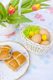 Easter table, basket, eggs and hot cross buns. Easter decorations, white wicker basket filled with eggs and cute little chicks, hot cross buns on a plate and Stock Image