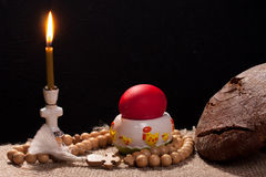Easter table. A table with a burning candle and a painted egg on a sack-covered table stock photo