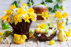 Easter table decoration. With fresh daffodils,chick and eggs Royalty Free Stock Photography